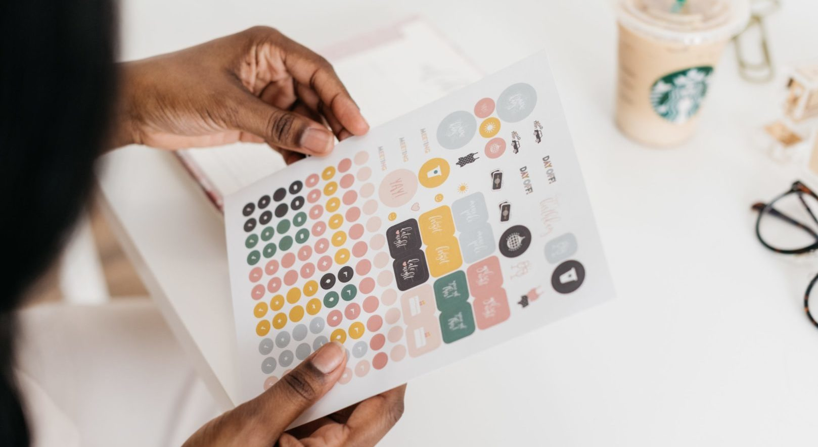 Person holding a sheet of planner stickers